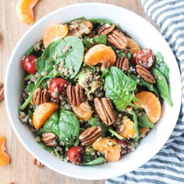 Salad made of spinach, lentils, quinoa, oranges, and pecans in a white bowl.
