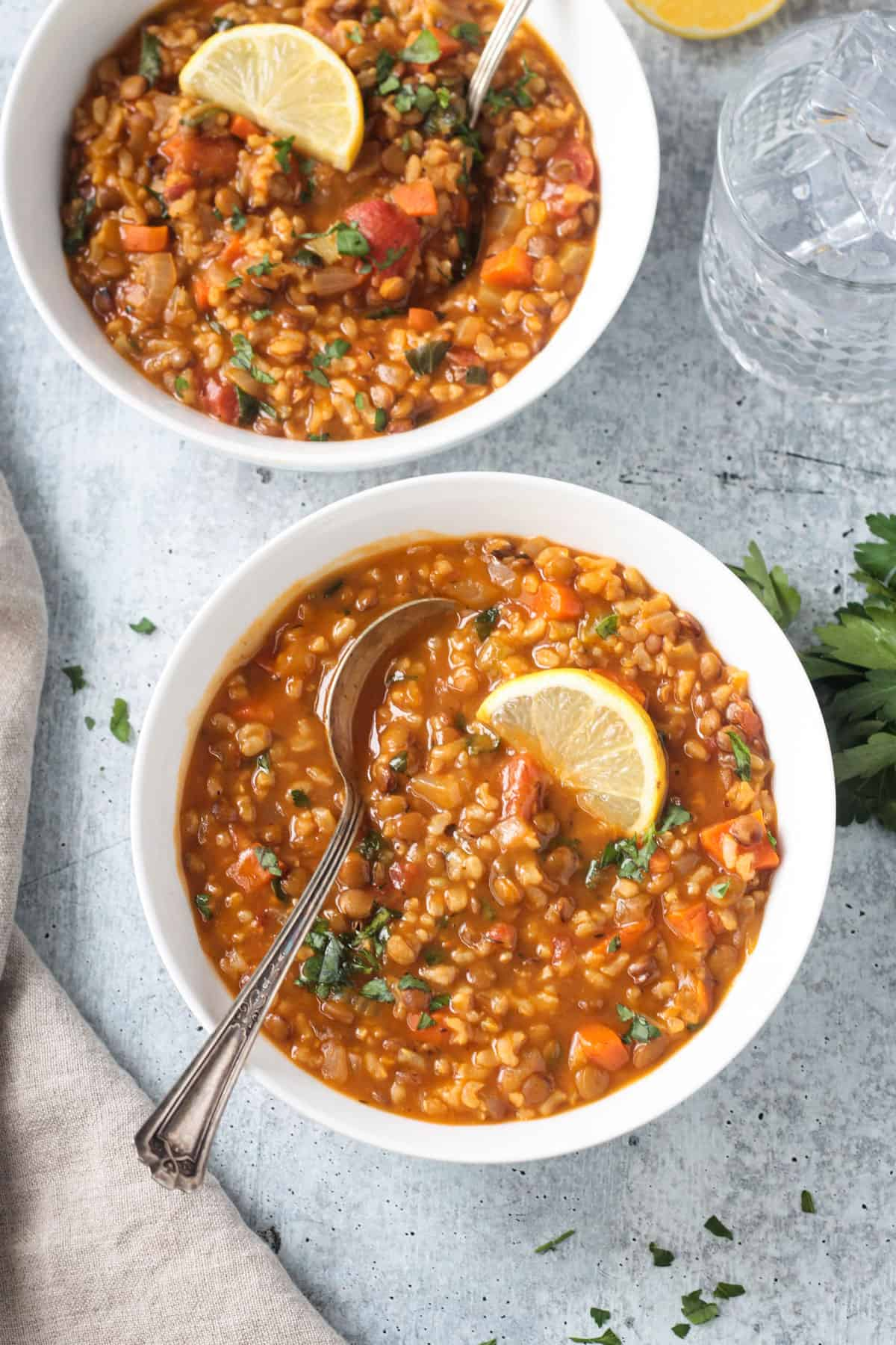 Two bowls of lentil rice soup on a table.
