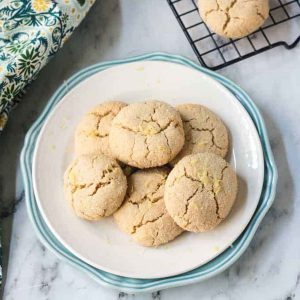 Pile of Lemon Crinkle Cookies on a white plate.