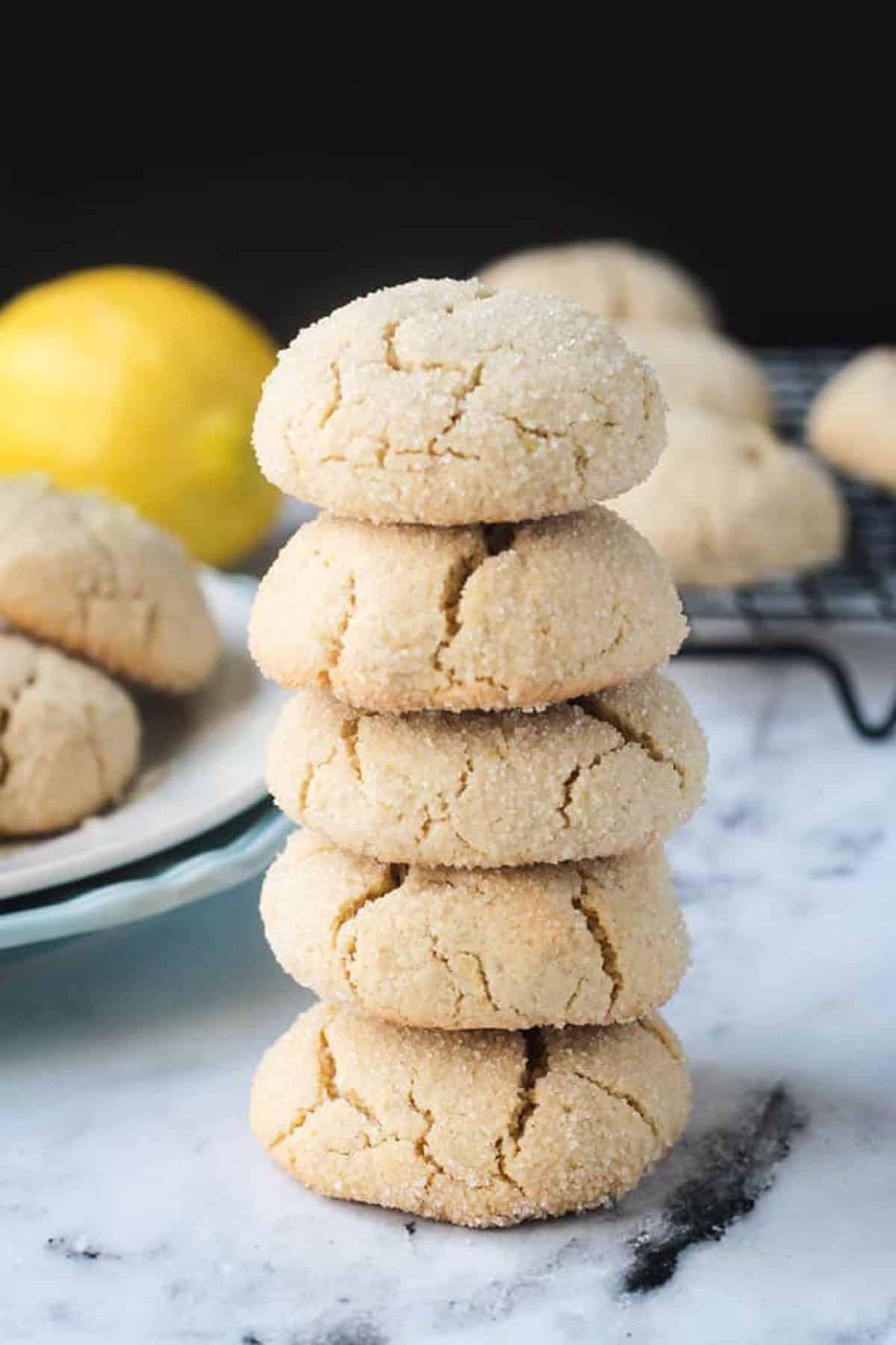 Stack of 5 lemon crinkle cookies on a white marble background.