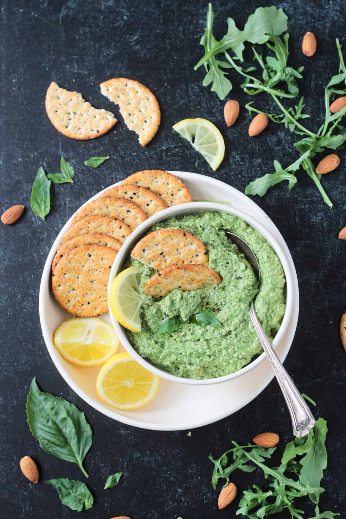 Pumpkin seed pesto in a bowl on a plate with crackers and two lemon halves.