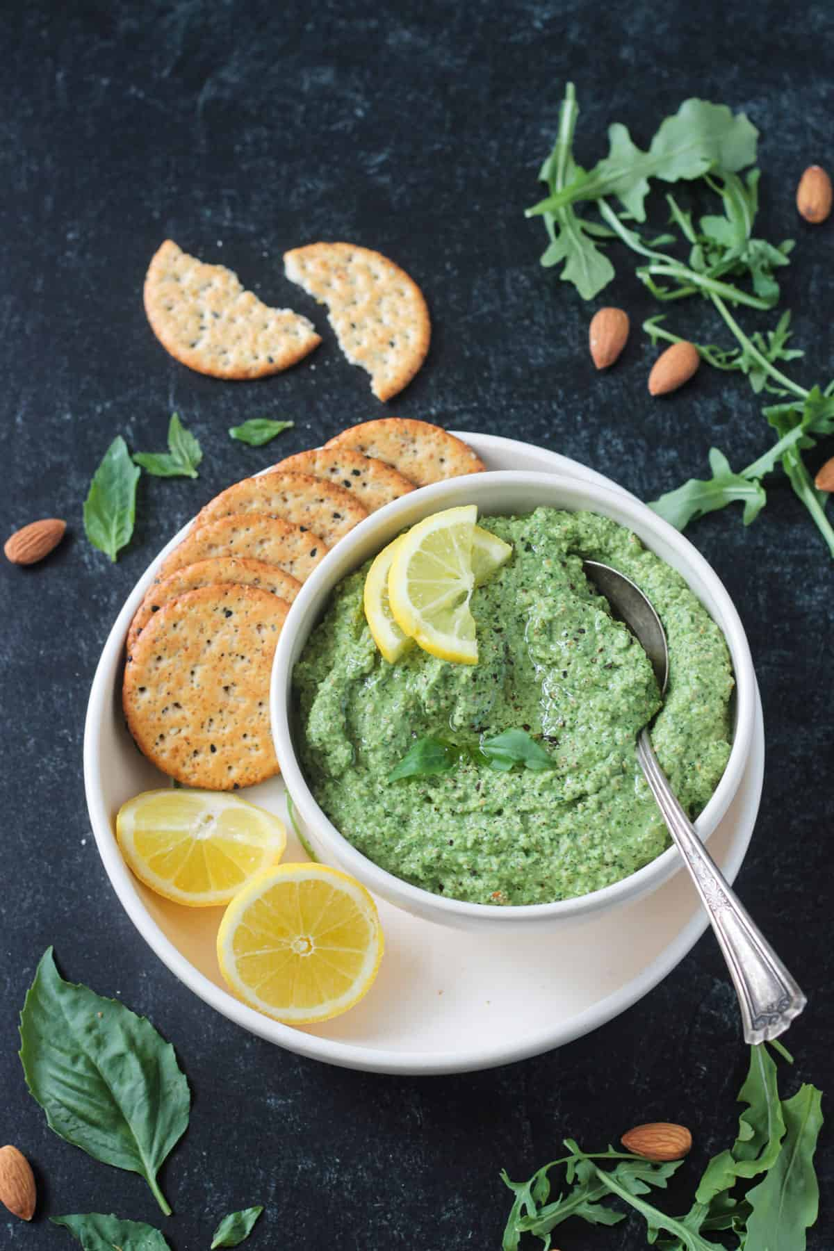 Spoon in a bowl of pesto next to crackers.