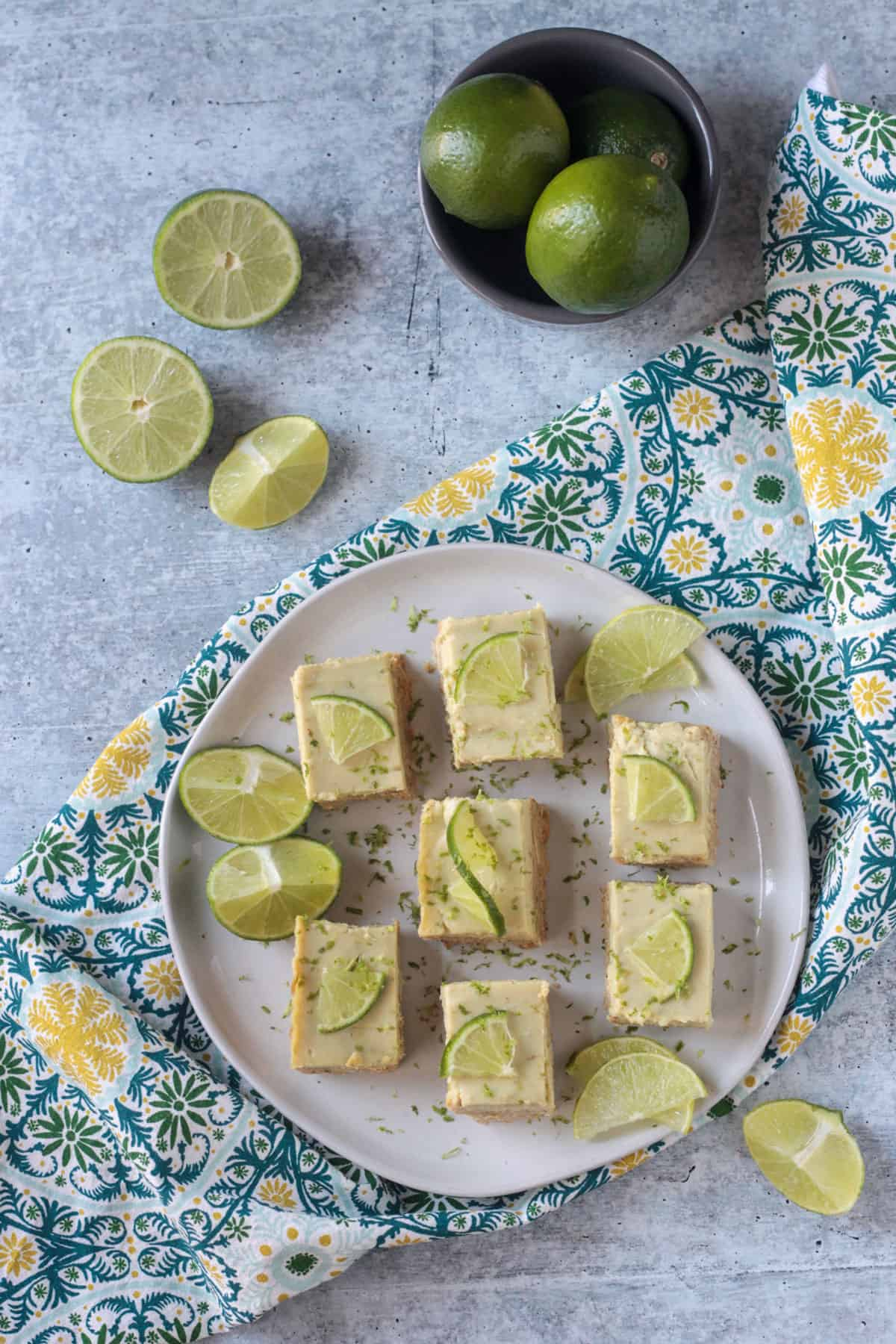 7 vegan lime bars on a plate topped with lime zest.