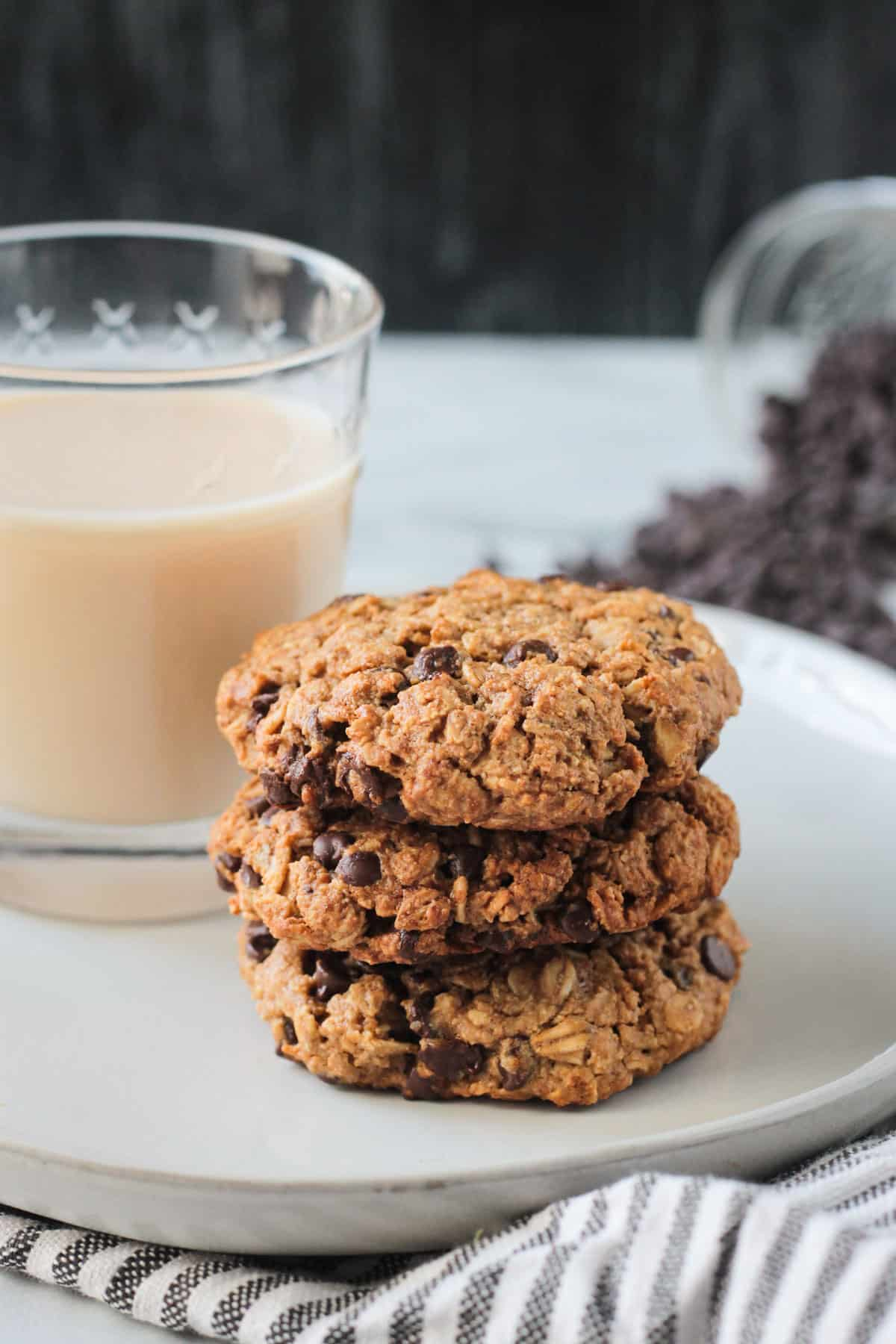 Stack of 3 cookies next to a glass of milk.