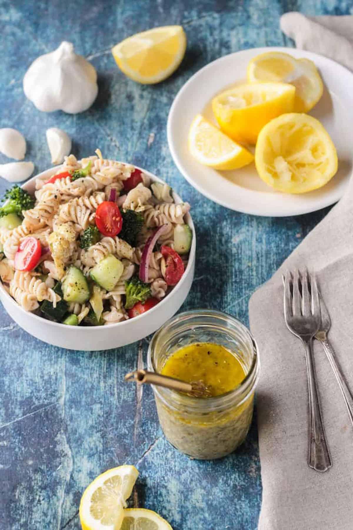 Small bowl of pasta salad next to a jar of vinaigrette and lemon slices.