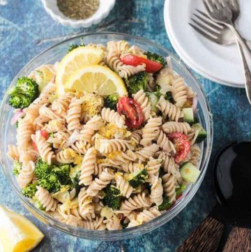 Bowl of vegan pasta salad with rotini noodles, broccoli, cucumber, artichokes, and tomatoes.