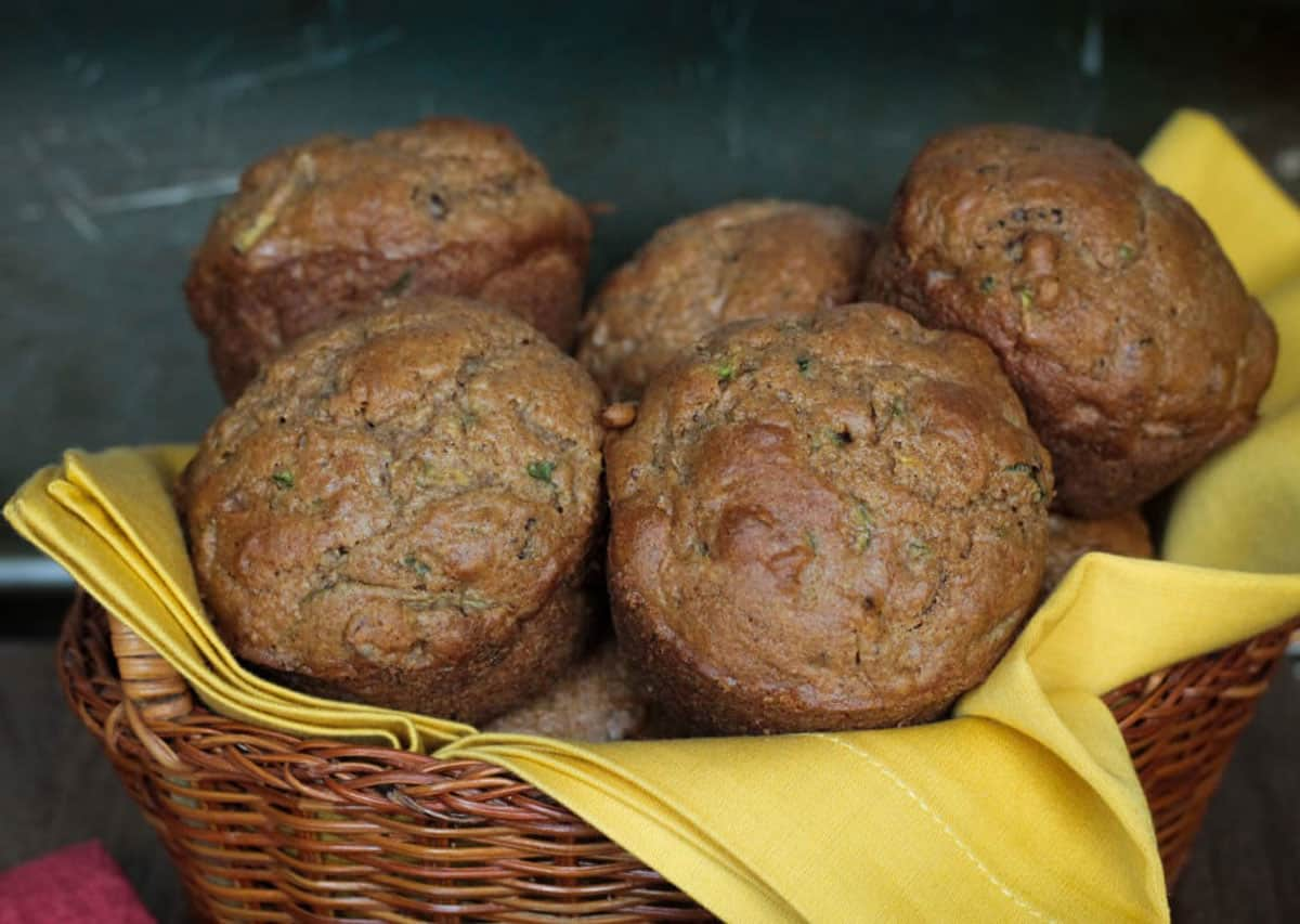 Pile of green flecked brown muffins in a wicker basket lined with a yellow towel.