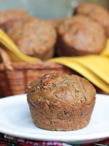 One muffin on a white plate in front of a basket of vegan zucchini muffins.