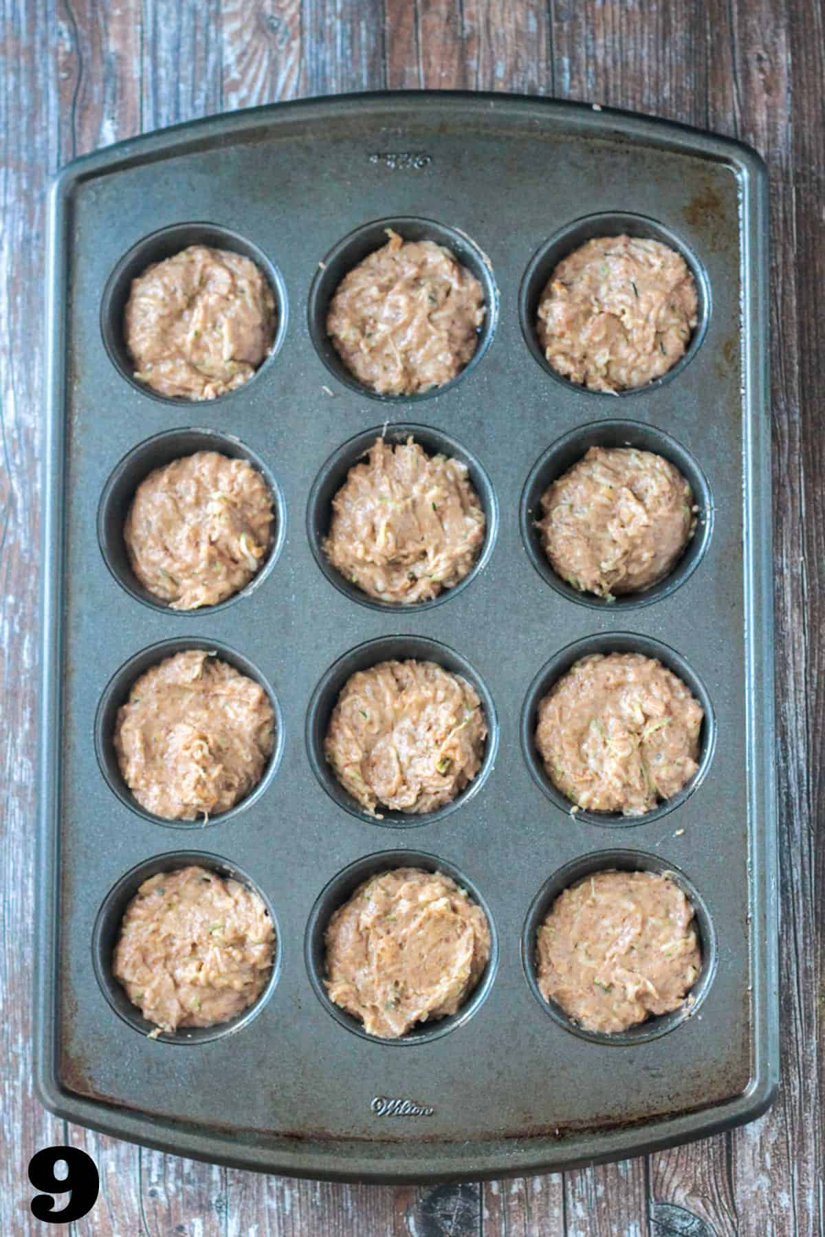 Raw batter in a 12-cavity muffin tin ready to be baked.