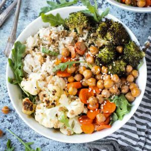 Dinner bowl of rice, cauliflower, broccoli, carrots, and chickpeas topped with a sprinkle of sesame seeds.