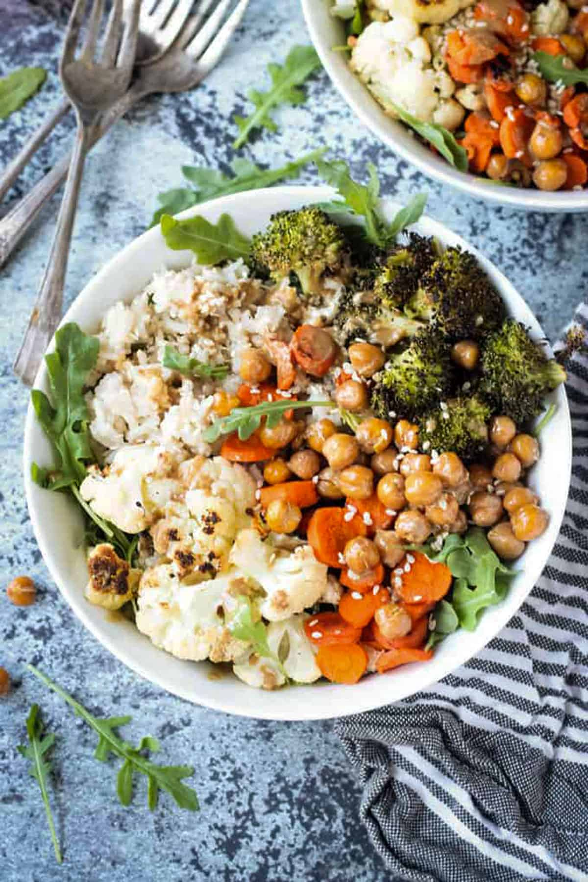 Bowl of rice, cauliflower, broccoli, carrots, and chickpeas topped with a sprinkle of sesame seeds.