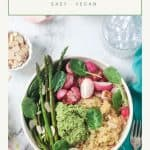 Quinoa veggie bowl with asparagus, radishes, fresh spinach, and pesto in a white flat bowl.
