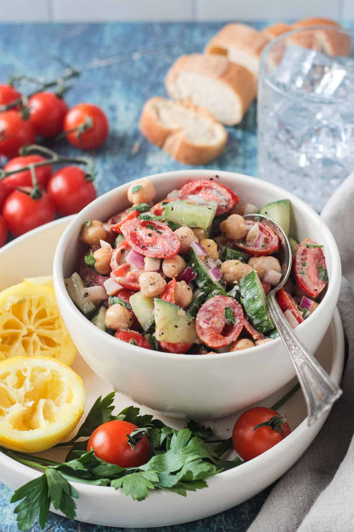 White bowl with tomatoes, chickpeas and cucumbers drizzled with tahini dressing.