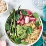 Roasted asparagus spears next to radishes and pesto on top of a quinoa bowl.