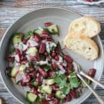 Red kidney bean salad on a gray plate with a baguette slice.