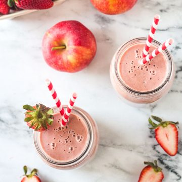 Overhead view of two glasses filled with strawberry smoothies on a white marble counter.