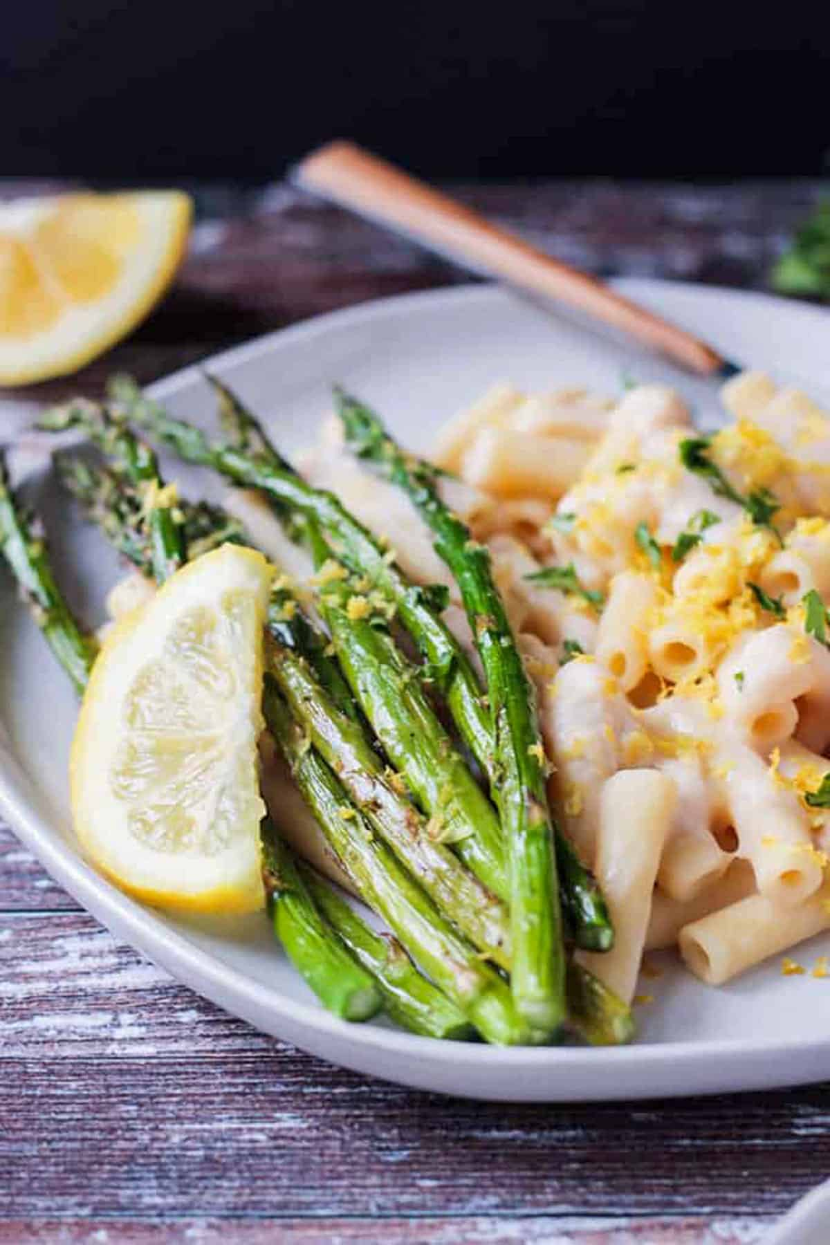 Close up of roasted asparagus topped with lemon zest and a lemon wedge.