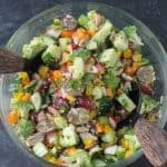 Chopped raw veggies mixed with vinaigrette in a glass bowl.