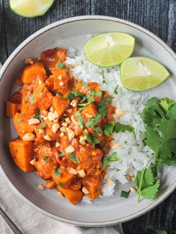Sweet potato peanut butter curry with jasmine rice garnished with cilantro and two lime wedges.