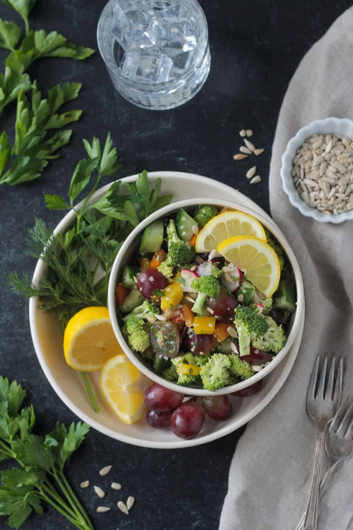 Bowl of salad on a plate with fresh herbs, lemon wedges, and a bunch of red grapes.