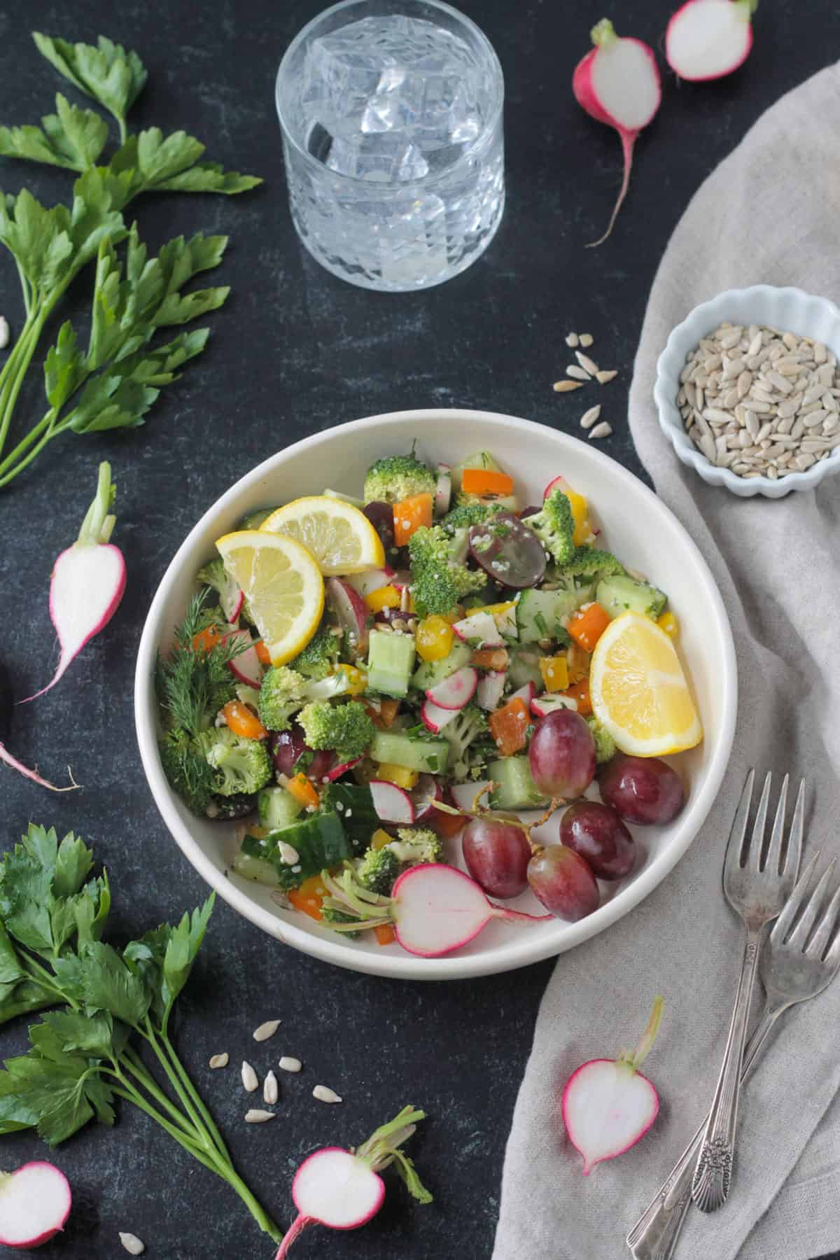 Raw Veggie Chopped Salad in a white bowl garnished with two lemon wedges.