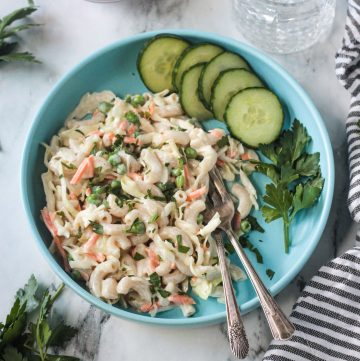 Vegan Macaroni Salad on a blue plate with two forks and a side of sliced cucumbers.