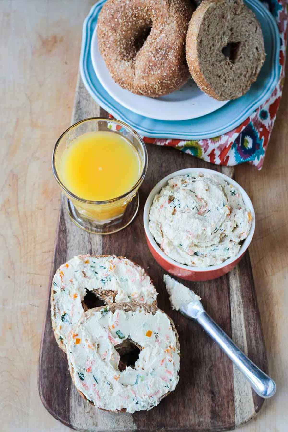 Plate of bagels next to a glass or orange juice and two bagel halves with veggie spread.