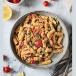 Overhead view of a finished dish of creamy rotini, spinach & tomatoes in a gray bowl.