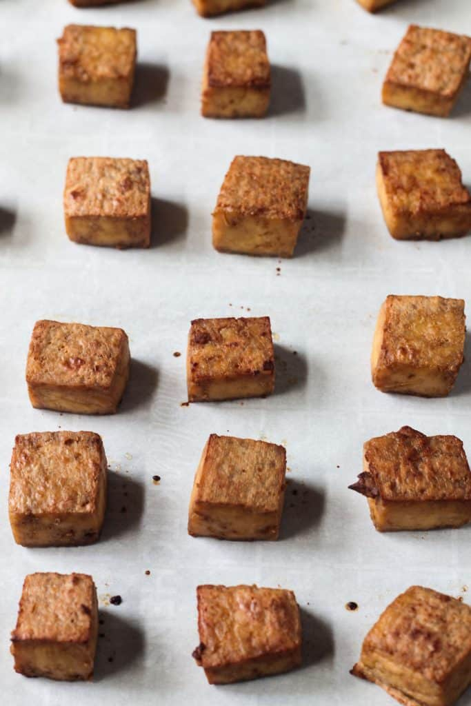 Oven baked tofu with crispy edges on parchment paper