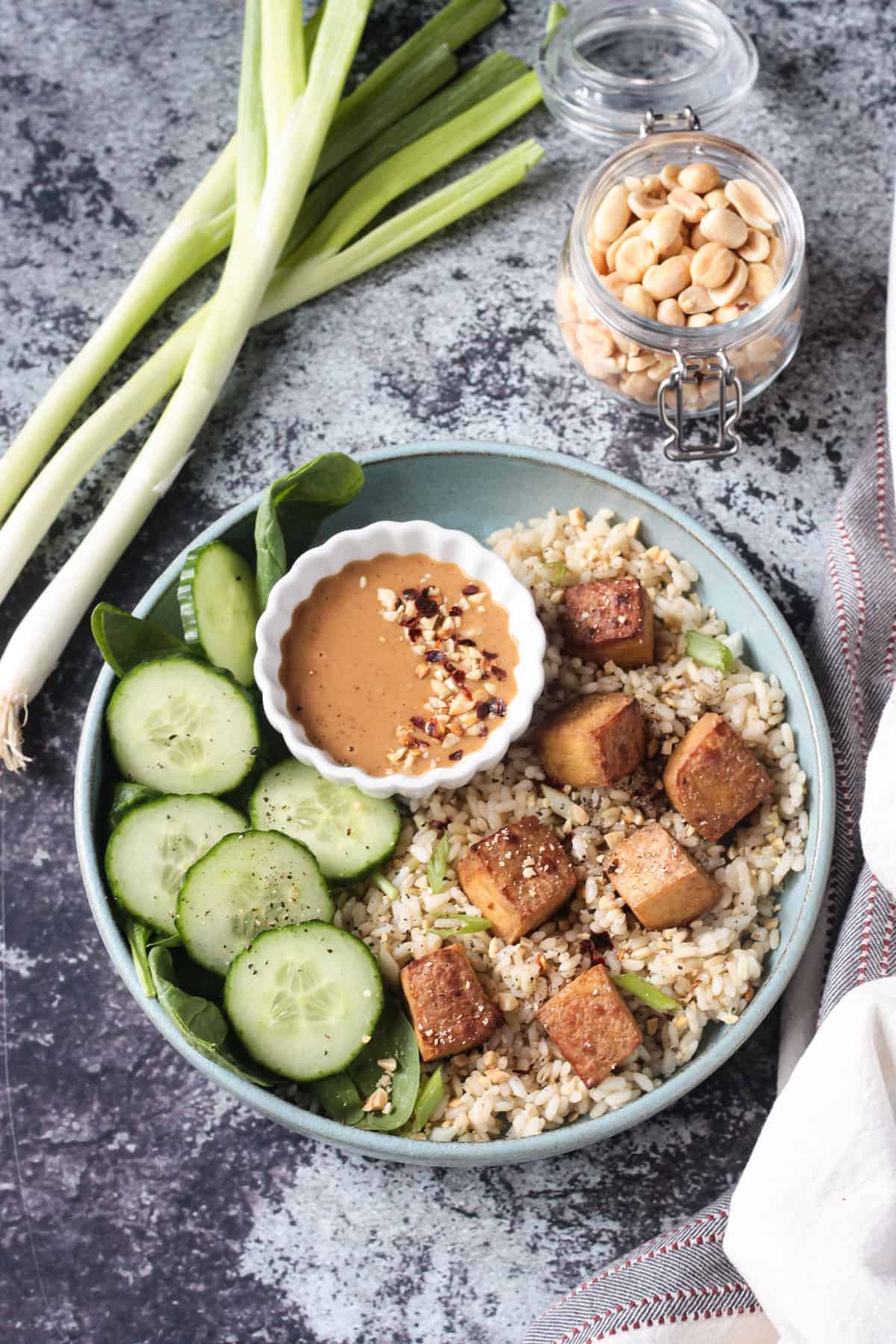 Baked tofu over rice with a side of cucumbers and peanut sauce.