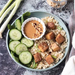 Oven baked tofu finished dish with rice, cucumbers, and sauce.