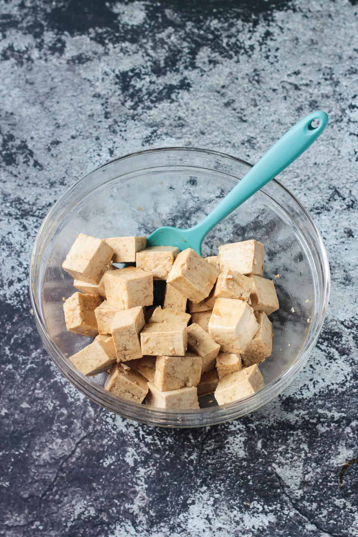 tofu cubes marinating in a glass bowl