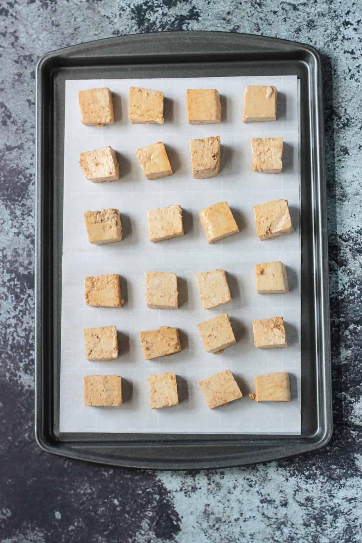 marinated tofu cubes on a sheet pan ready to go in the oven