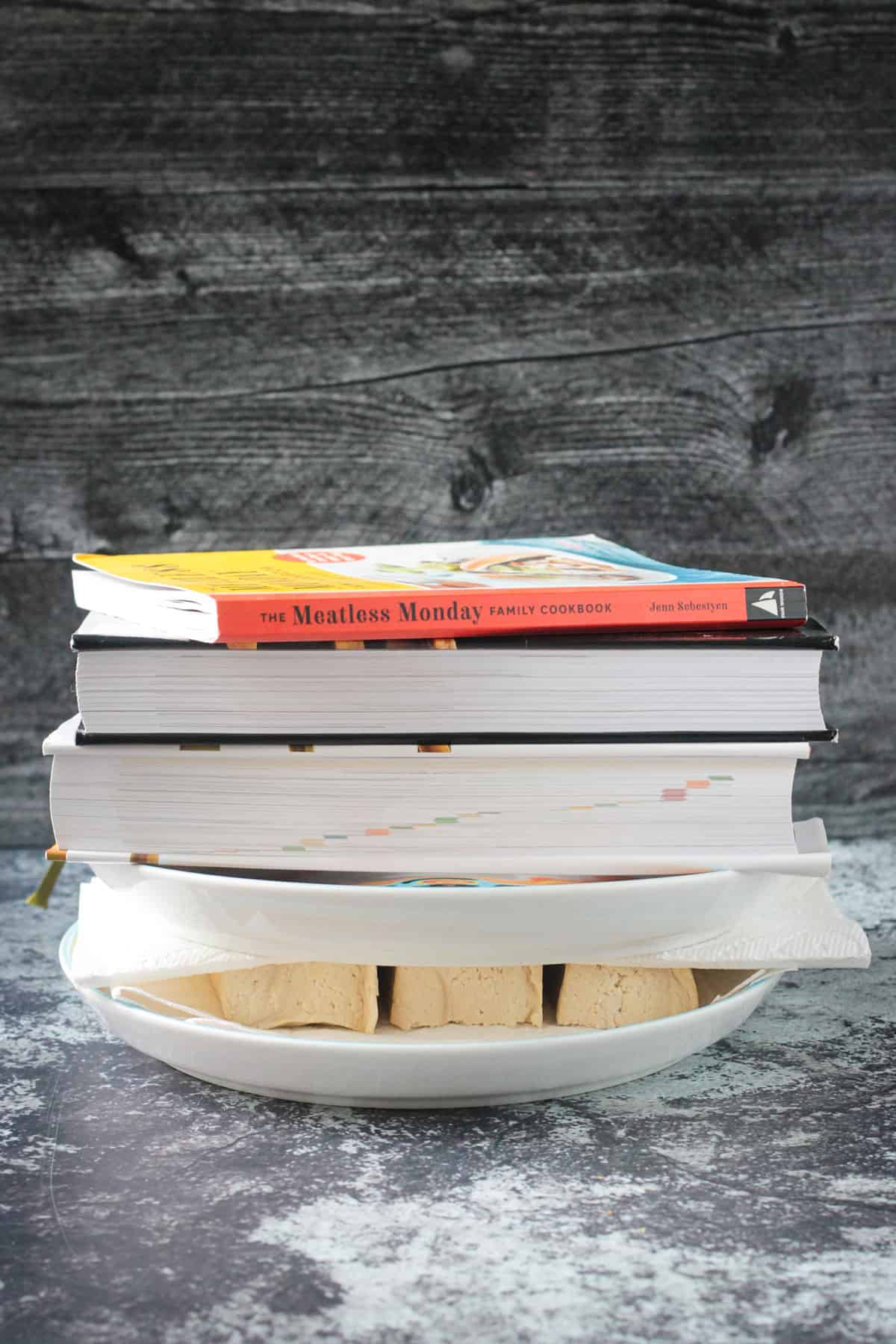 Pressing tofu slices between two paper towel lined plates weighted down with books.