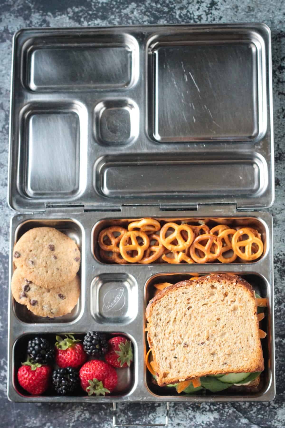 Vegan lunch box with hummus veggie sandwich, strawberries, blackberries, pretzels, chocolate chip cookies.