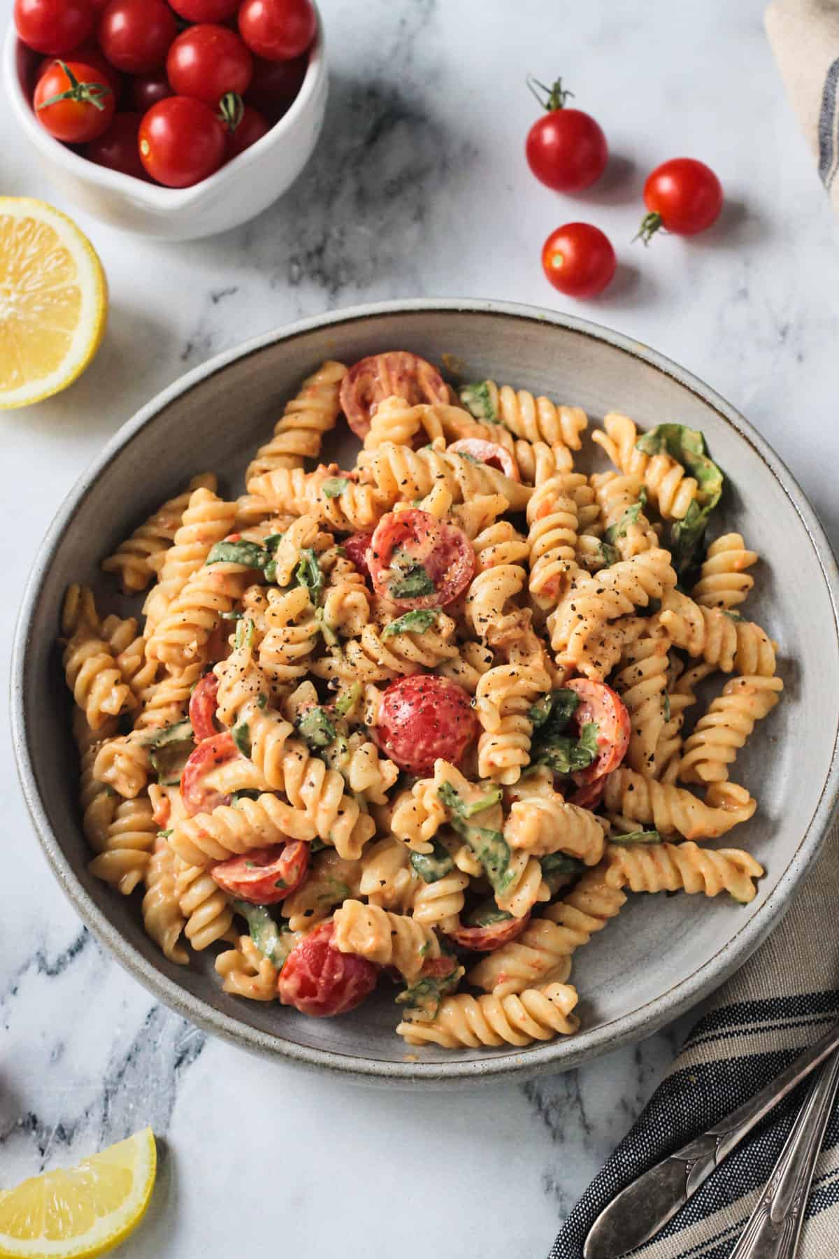 Rotini pasta in creamy sauce with tomatoes and spinach in a gray flat bowl.