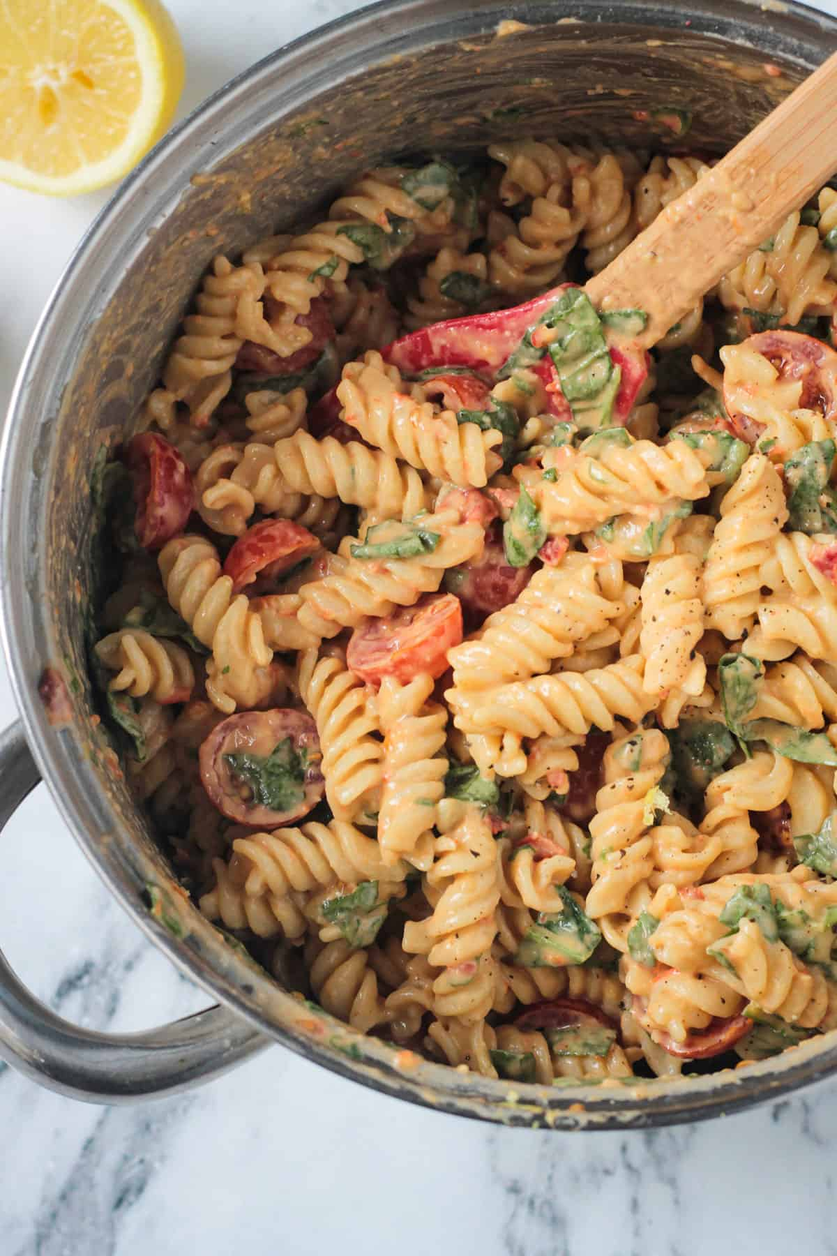 Red spatula stirring noodles in a pot with sauce, tomatoes, & spinach.