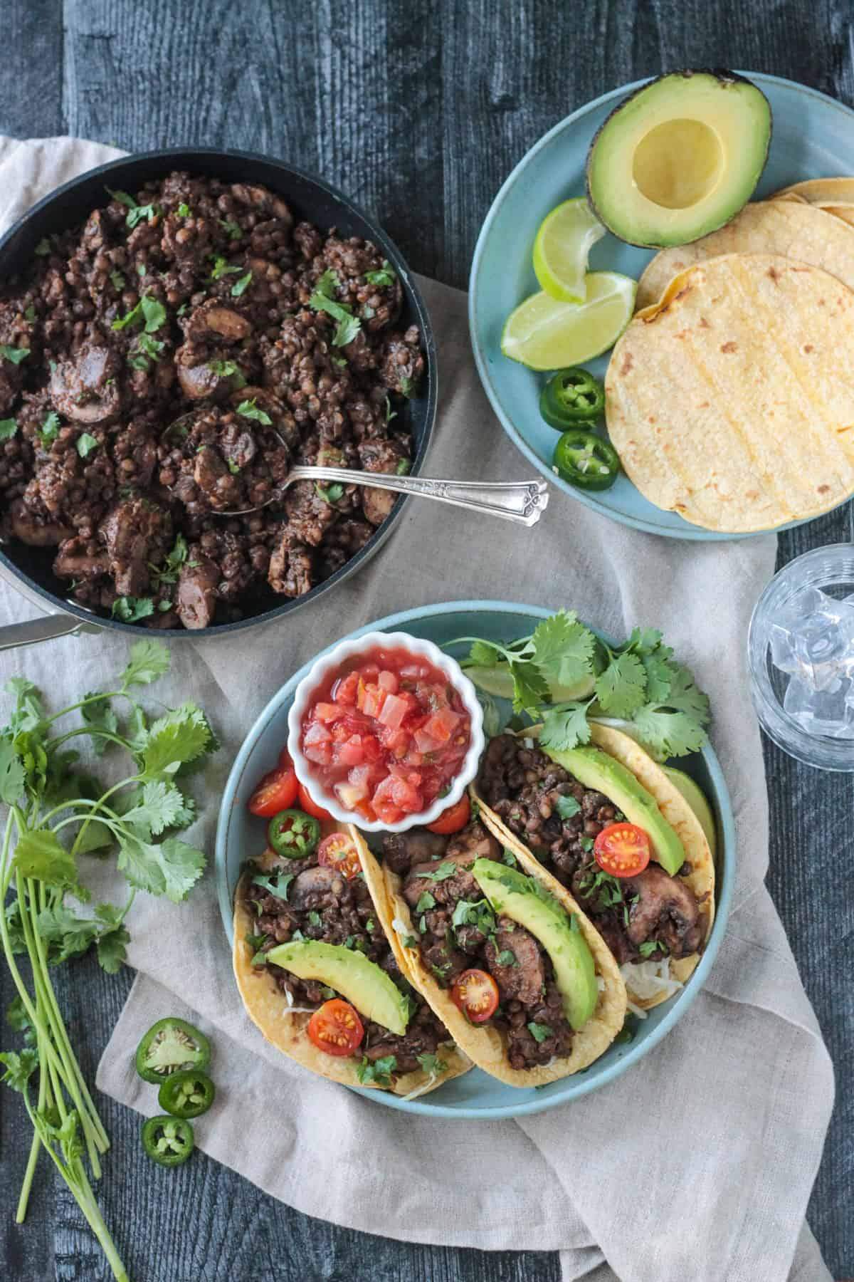 Lentil mushroom taco meat in a skillet next to a plate of tacos.