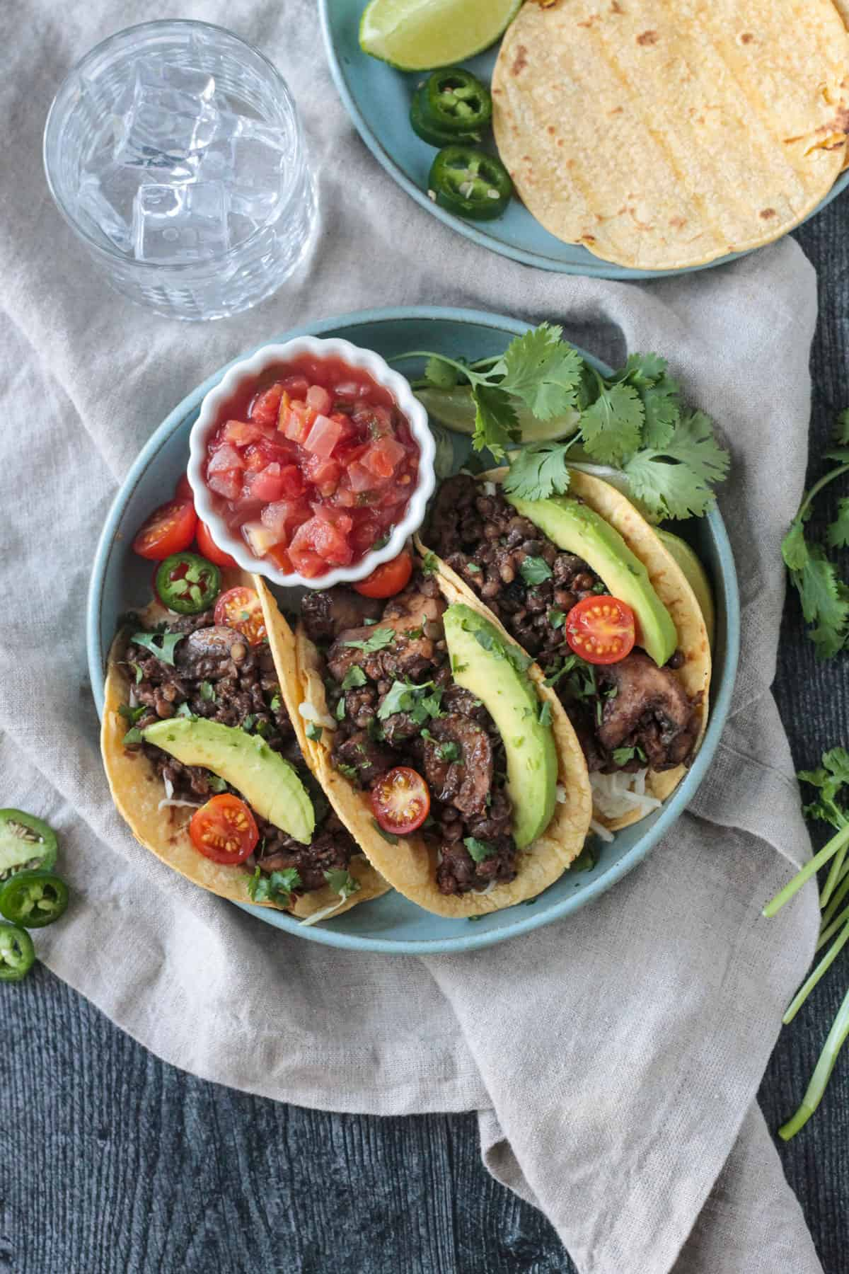 Three vegan lentil tacos with mushrooms and toppings next to a small bowl of salsa.