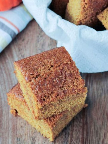 Two squares of dairy free cornbread stacked in front a basket of more.