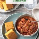 Two squares of cornbread on a plate next to a bowl of chili.