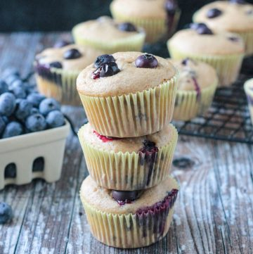 Stack of 3 vegan banana blueberry muffins in paper wrappers.