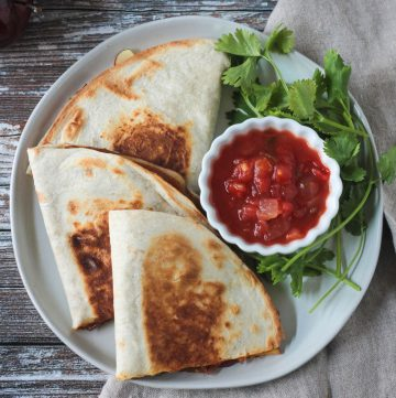 Overhead view of three halved vegan quesadillas next to a small bowl of salsa.