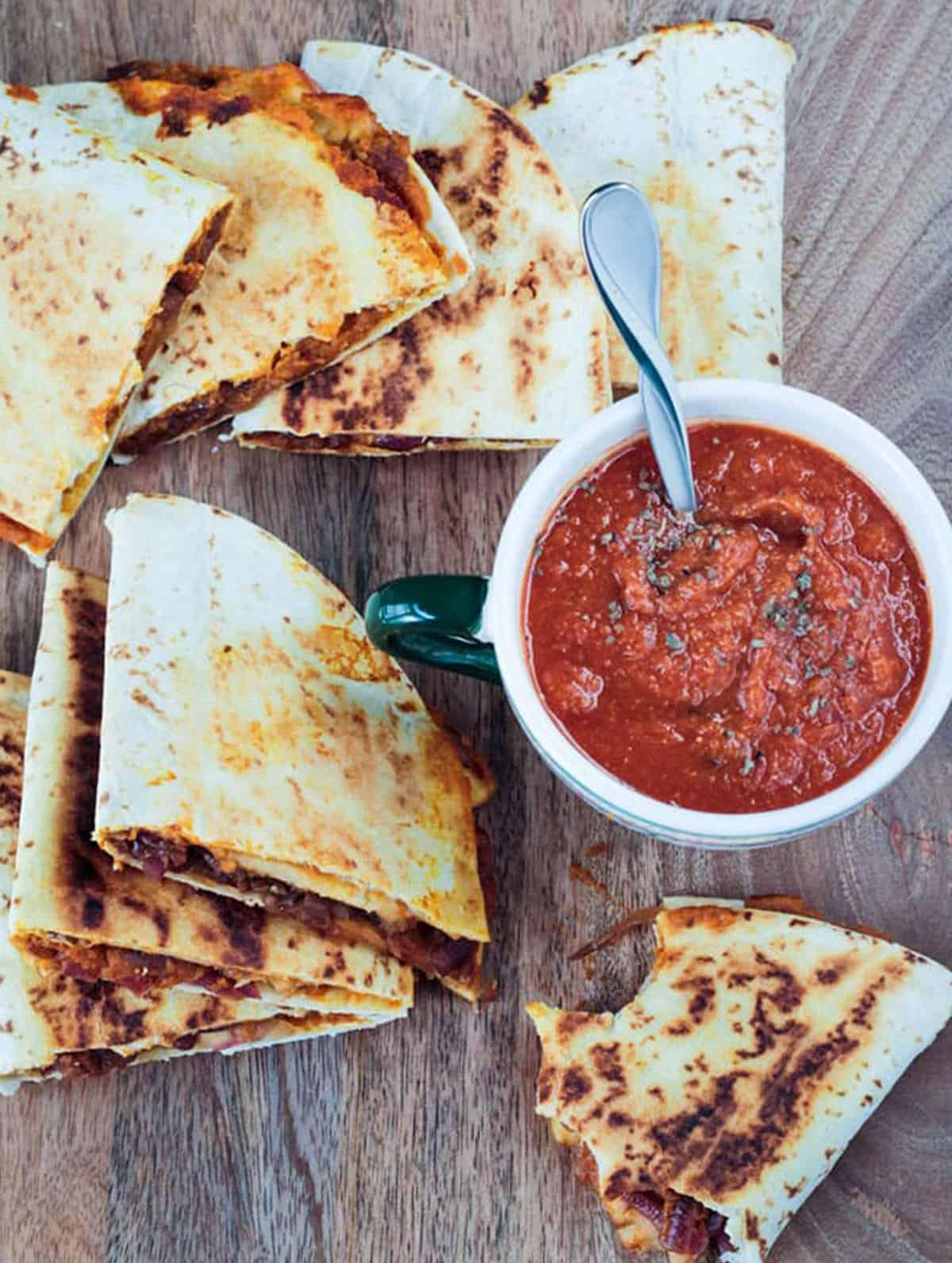 Several quesadilla halves surrounding a bowl of tomato soup.