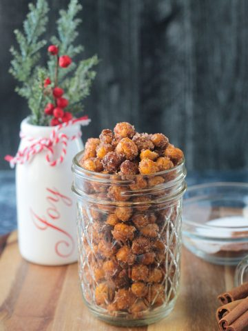 Cinnamon sugar crunchy chickpeas in a glass jar in front of a holiday vase.