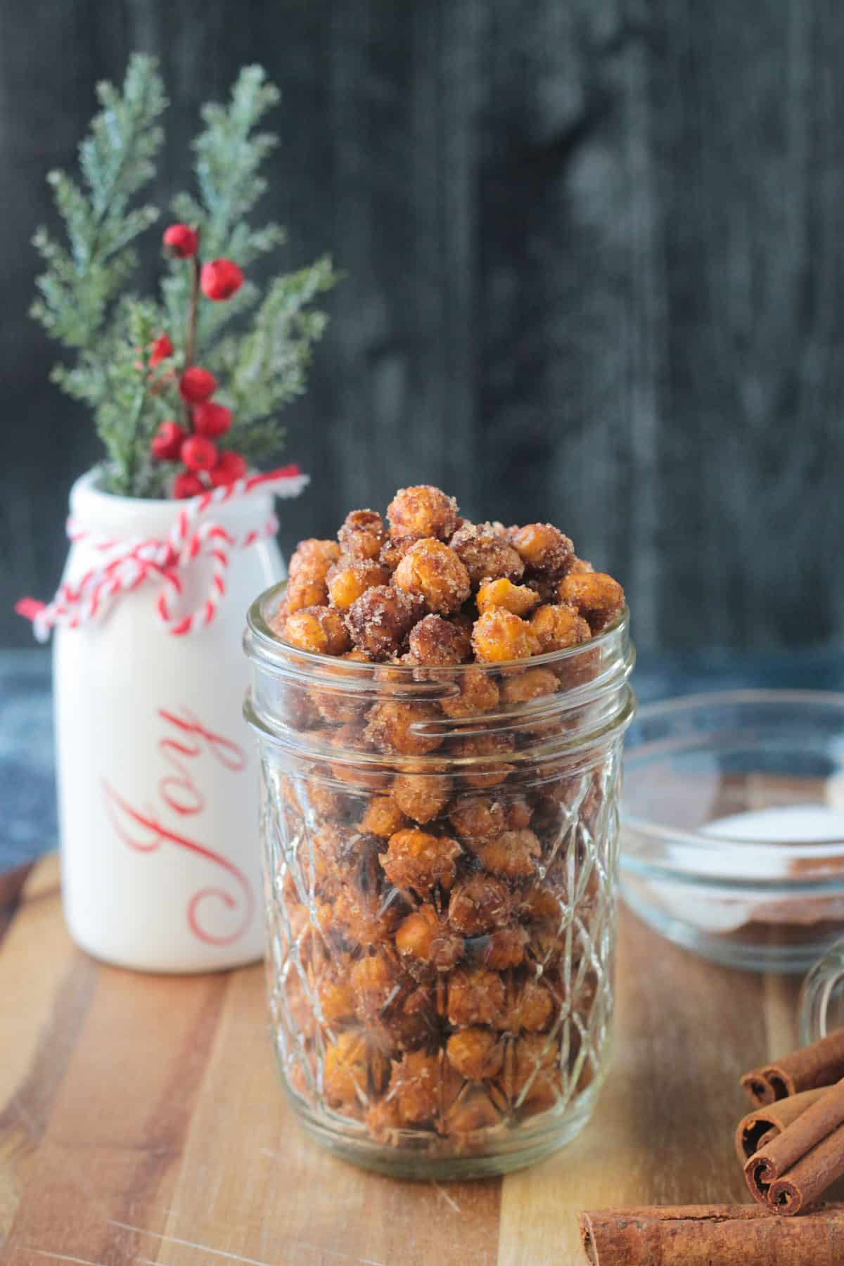 Cinnamon sugar crunchy chickpeas in a glass jar in front of a white vase.