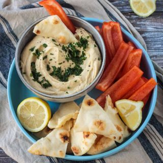 Bowl of hummus next to pita triangles and red bell pepper strips.