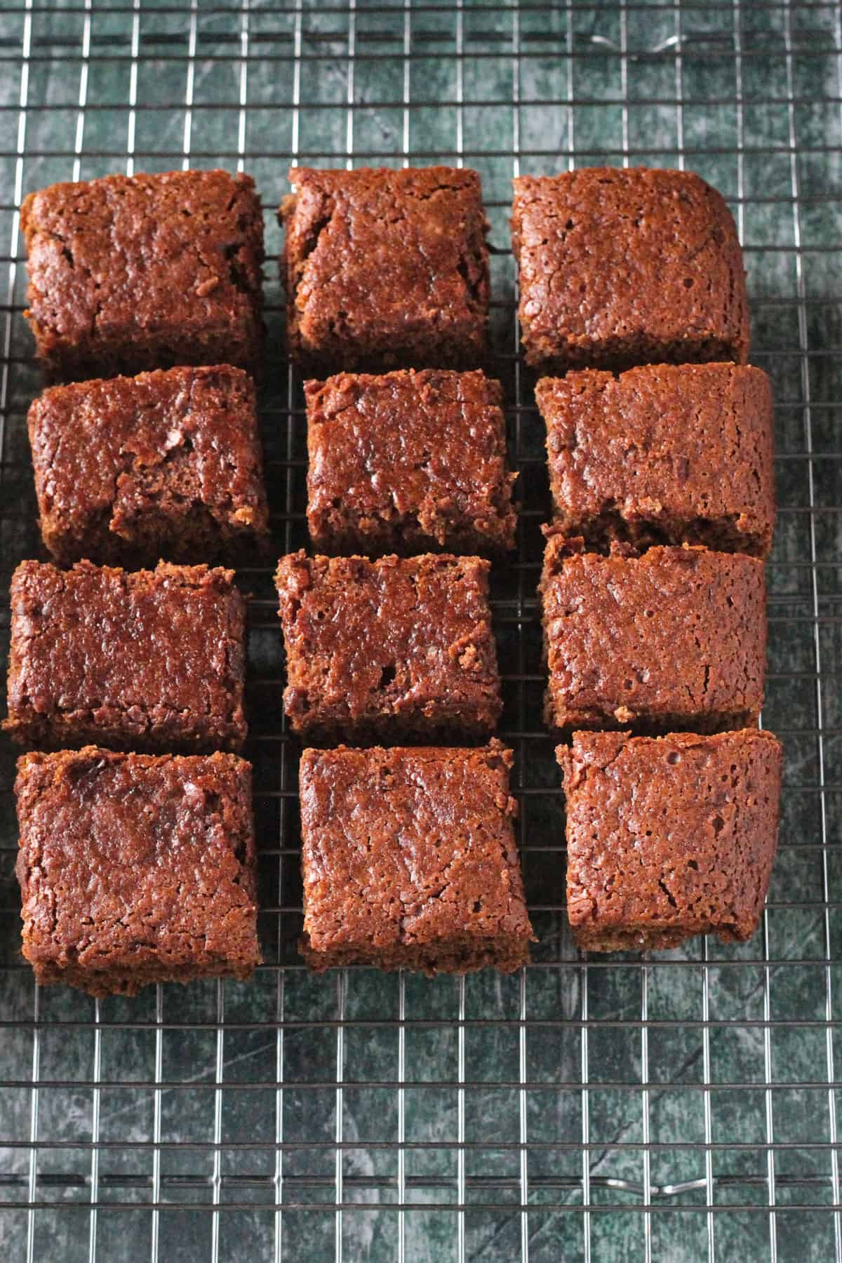 Squares of gingerbread cake on a wire cooling rack.