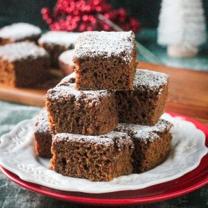 Stack of several gingerbread cake squares on a white plate dusted with powdered sugar.
