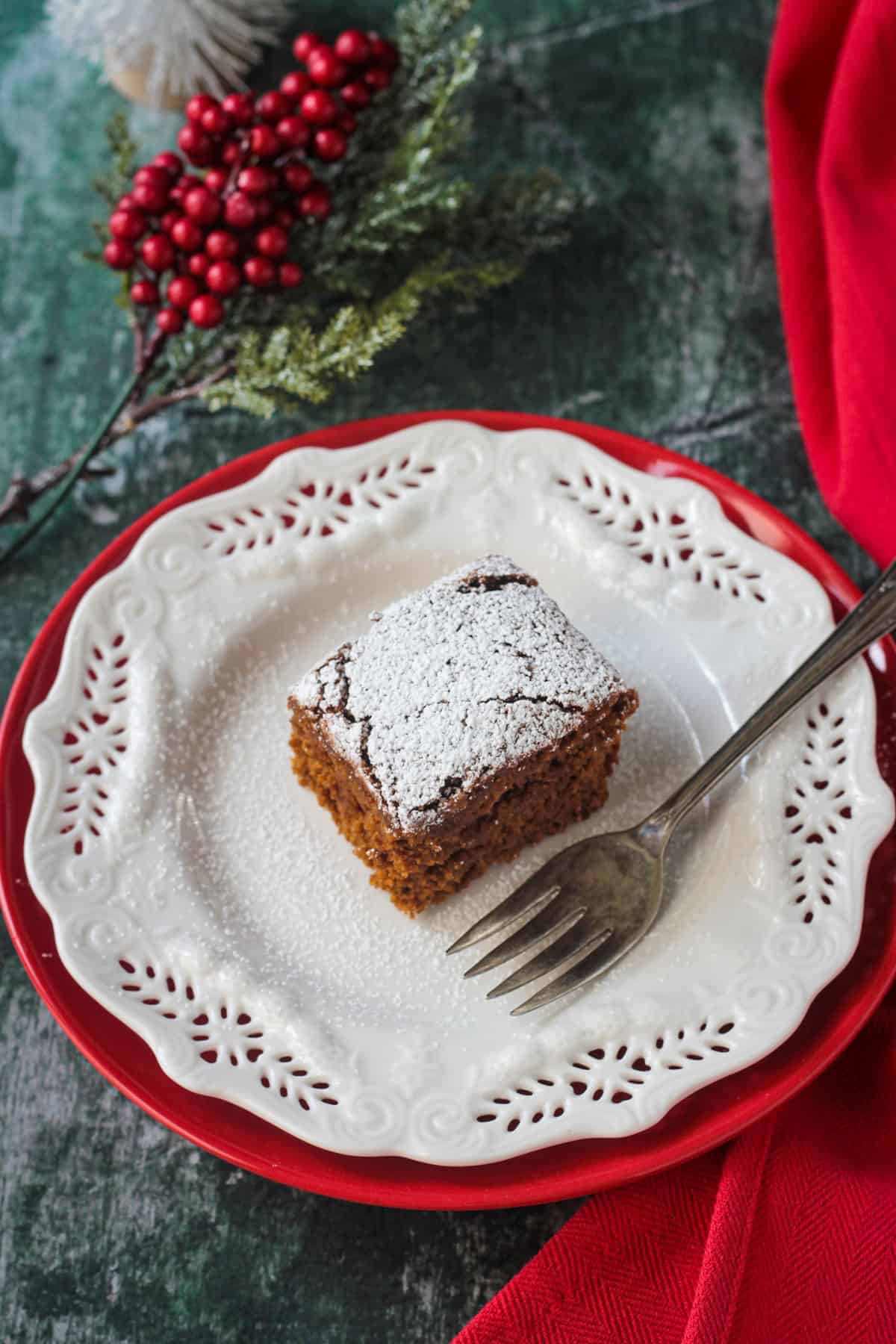 Powdered sugar dusted cake on a white plate with a fork.